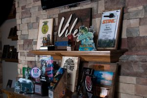 Many custom awards lined up on a table and shelf